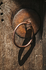 Rusty iron fittings hardware of old weathered wooden board of door