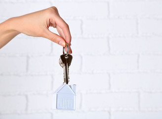 Female hand holding keys with house key chain on white brick wall background