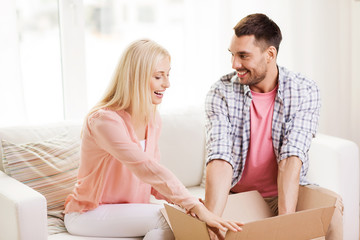 happy couple with open parcel box at home