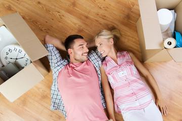 happy couple lying on floor among cardboard boxes