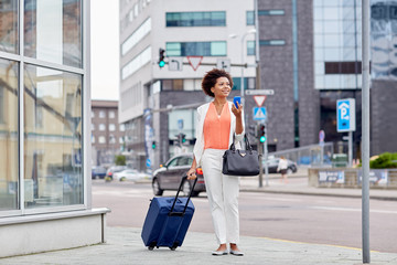 happy african woman with travel bag and smartphone