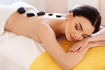 Spa Stone Massage. Young Woman Have Hot Stone Massage Treatments
