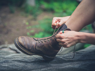 Young woman tyoing her boots in forest