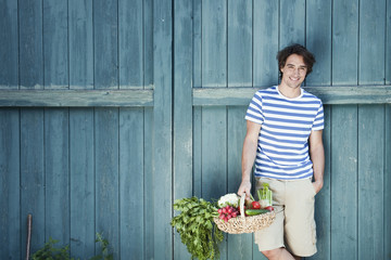 Germany,Bavaria,Man in front of barn door holding basket with fresh vegetables,smiling,portrait