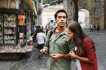 Portugal,Lisboa,Baixa,Rossio,young couple looking at postcard