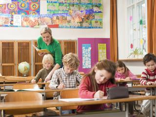 Children writing exam in the classroom