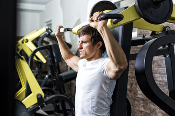 Austria,Klagenfurt,Man in fitness center doing machine workout