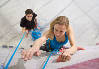Germany,Bavaria,Munich,Young woman bouldering while man holding rope