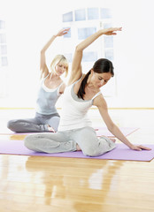Germany,Hamburg,Yoga instructor and woman doing yoga exercise in gym room