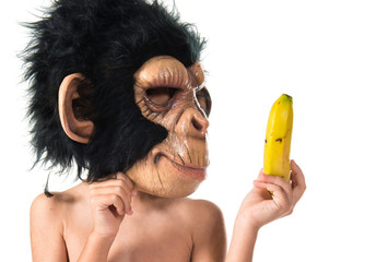 Child with monkey mask showing his banana