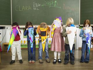 Children (4-7) standing in front of blackboard looking in to school cones