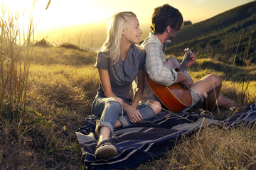 Young couple with guitar on blanket in meadow