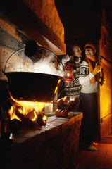 Couple in alpine hut near fireplace,man holding lamp