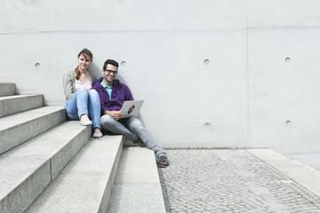 Germany,Berlin,Couple using laptop on stairway