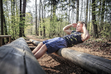 Germany, Coburg, Young man exercising sit ups on a fitness trail in a forest