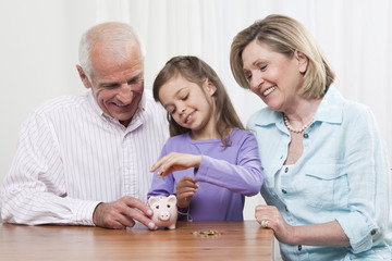 Granddaughter (6-7) and grandparents with piggy bank,smiling
