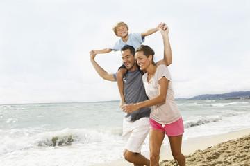 Spain,Family walking on beach at Palma de Mallorca,smiling