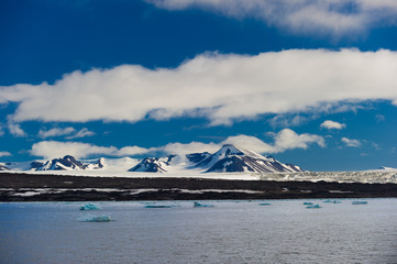 Blue green icebergs floating in a fjord in Svalbard, Norway.