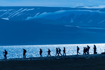Silhouetted group of hikers in Barentsoya, Svalbard, Norway.