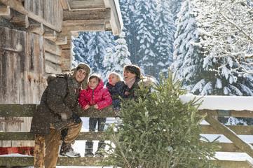 Austria,Salzburg Country,Flachau,Family leaning on fence in snow