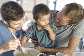 Gay couple baking cake with son