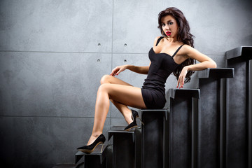 Fototapete - Sexy brunette woman sitting on stairs