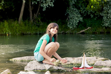 Girl playing with wooden toy boat at a river