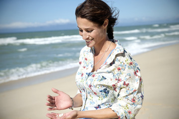 South Africa, portrait of smiling woman looking at shells in her hand