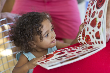 Little girl with curly hair looking at picture book