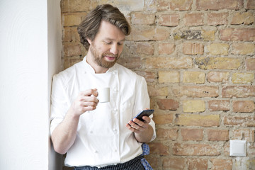 Cook with espresso cup and smartphone having a rest
