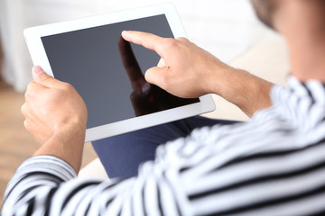 Male hand holding PC tablet on home interior background