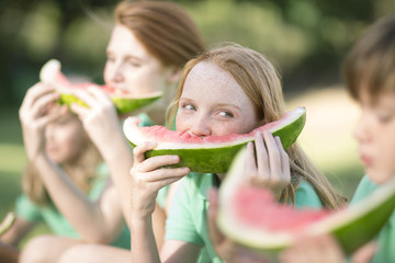 Portrait of girl eating slice of watermelon watching boy