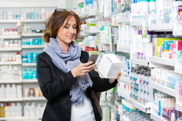 Smiling Customer Scanning Product Through Cell Phone In Pharmacy