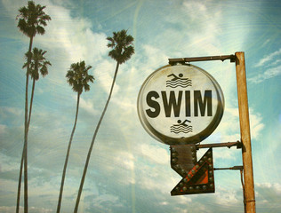 aged and worn vintage photo of swim sign at beach