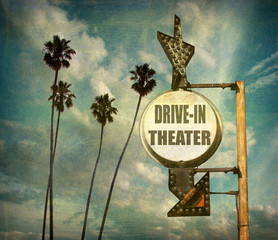 aged and worn vintage photo of drive in theater sign with arrow