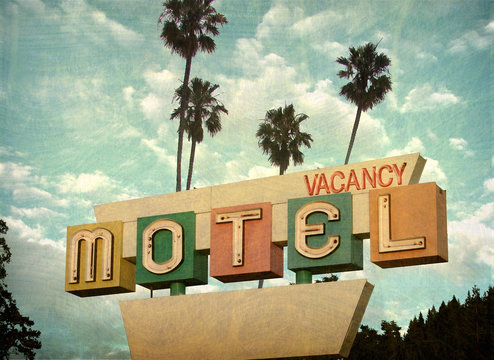 ged and worn vintage photo of retro motel sign with palm trees