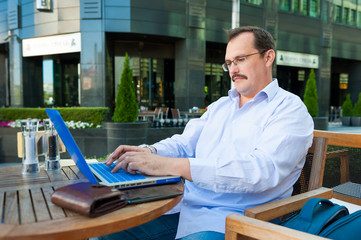 Middle age businessman works on laptop