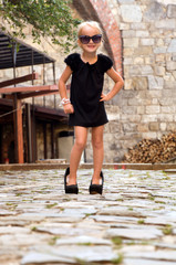 little girl wearing shoes and standing on the road