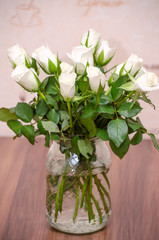 white roses in a glass vase on the table