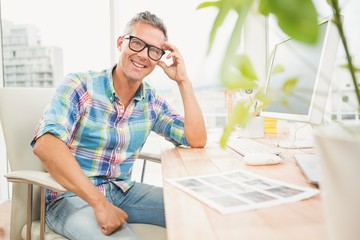 Smiling casual designer sitting on desk