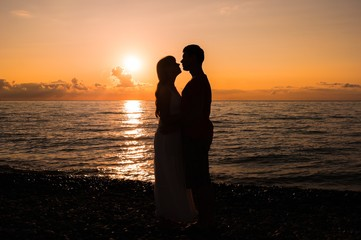 Two young lovers standing on a beach and looking to each other