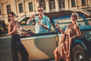 Wealthy friends drinking champagne near classic convertible