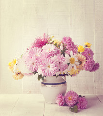 Retro still life with colourful chrysanthemums bunch on old  wooden board. Toned image