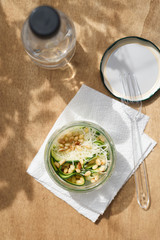 Home prepared healthy snack of zucchini, Parmesan cheese and pine nuts in jar on wooden background