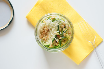 Zucchini carpaccio with Parmesan cheese and pine nuts in jar