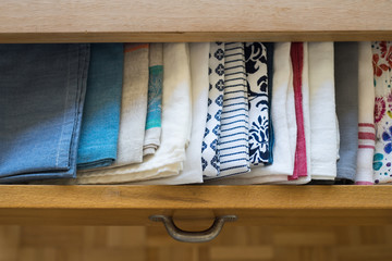 Tea towels arranged in a drawer of dining table