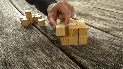 Closeup of businessman assembling blank wooden cubes into a stru