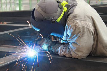 welder is welding steel structure with safety mask and safety gloves in factory