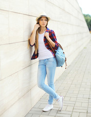 Pretty cool girl wearing a straw hat, shirt and backpack in the