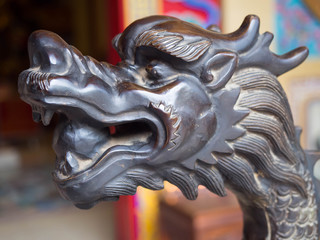 The carved wooden head of a black dragon in the public temple.